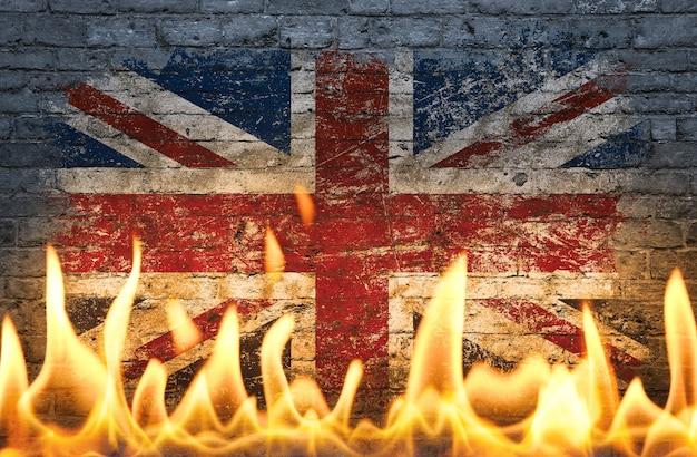 火事、危険、政治的、経済的危機またはパンデミックの世界の象徴として炎の中で描かれた英国の英国旗で壁をクローズアップ