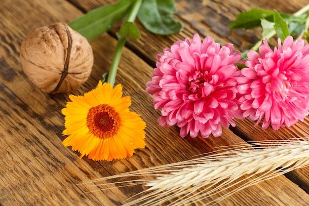 クローズアップクルミ、キンセンカとアスターの花、古い木の板の小麦の耳。浅い被写界深度。