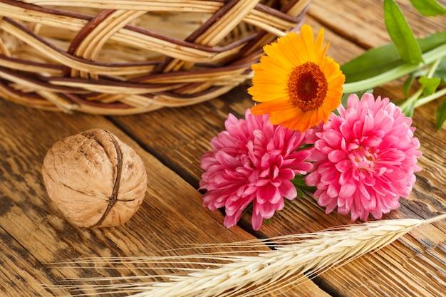 クローズアップクルミ、小麦の耳、キンセンカとアスターの花、古い木の板の籐のバスケット。浅い被写界深度。上面図。