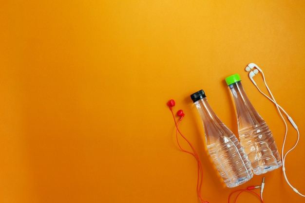 Close up of water bottle and earphones on orange color paper background,fitness background