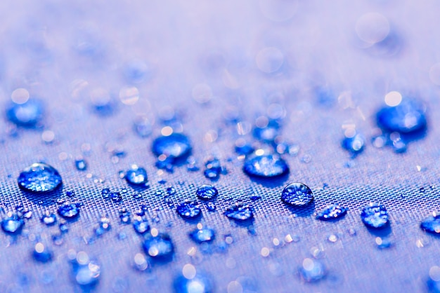 Close up water drops pattern over a blue waterproof cloth background