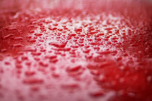 Close up water drops on red car serface for background