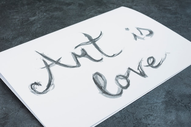 Close-up of watercolor hand drawn 'art is love' text on white paper