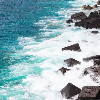 Close up wavy water at rocky seashore
