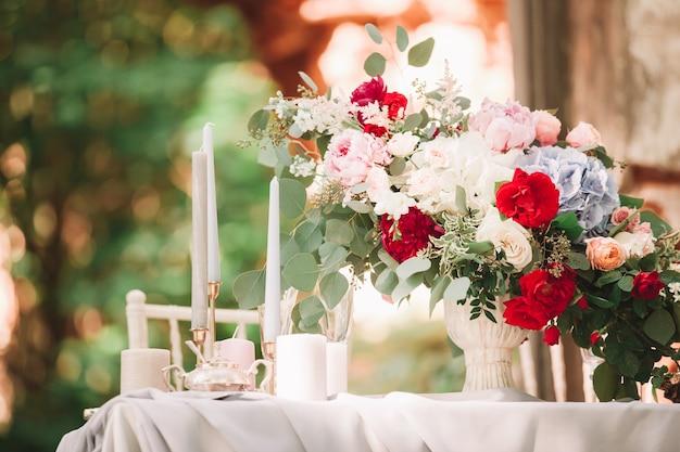 閉じる。結婚式のテーブルの上の結婚式の花束とキャンドル。コピースペース付きの写真