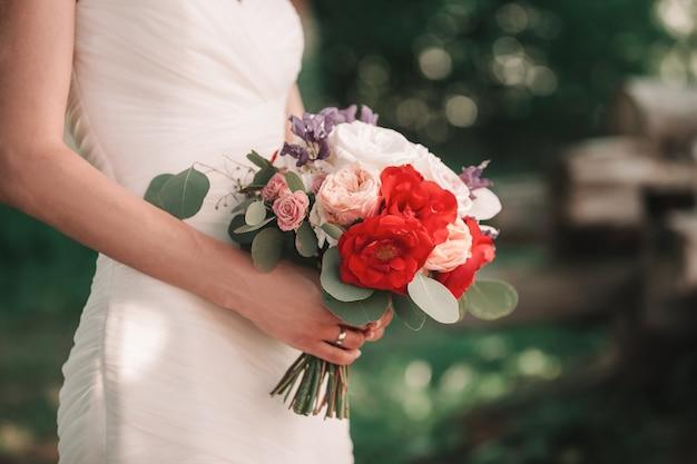 花嫁の手でクローズアップ。結婚式の花束。休日と伝統