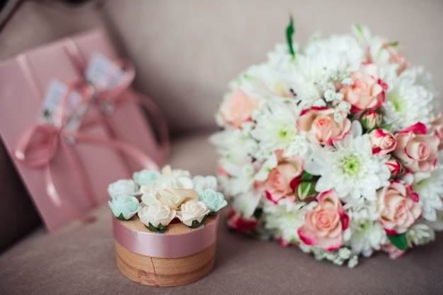 Close-up of a wedding bouquet of pink roses and white chrysanthemums on a space of pink certificates and a box on a powdery sofa