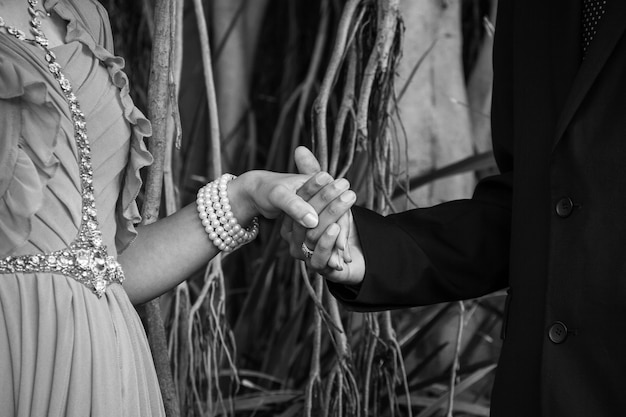 Close up on wedding couple holding hands in the park with tree branches and roots