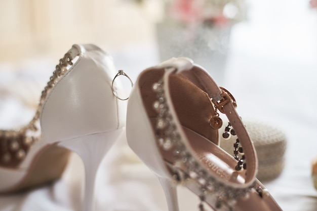 Close-up of wedding ring between white bridal shoes.