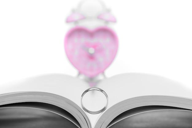 白い背景のピンクのハート型時計で結婚指輪を閉じます。