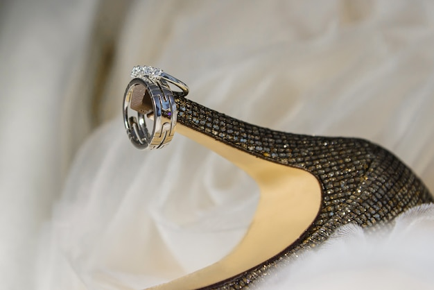 Close up of wedding rings on bride's shoes