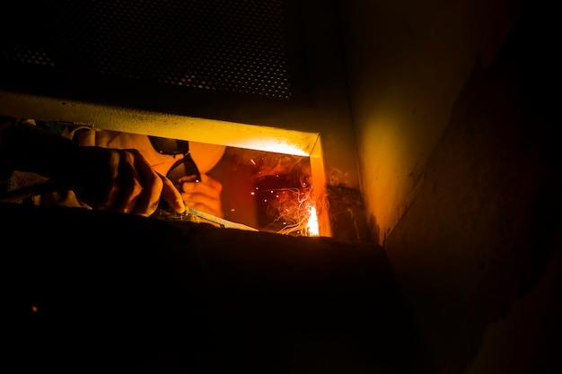 Закройте вверх дуговой сварки стали с искровым светом в темной комнате