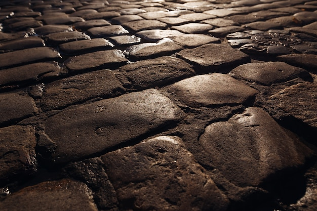 A close-up of wet old paving stones with the sun rays