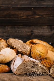 Close-up of wheat crop in front of baked bread on wooden table