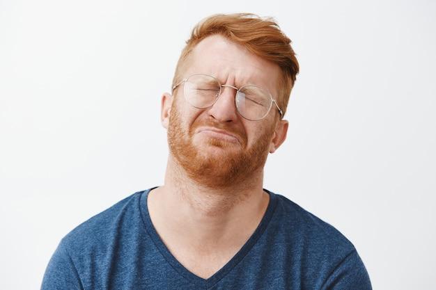 Primo piano dell'uomo barbuto rosso riluttante piagnucoloso che sembra miserabile, che si lamenta e che piange