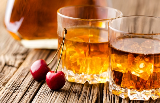Close-up whiskey glasses with ice and cherries