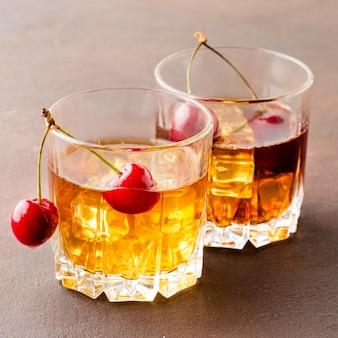 Whisky di primo piano sulle rocce con ciliegie