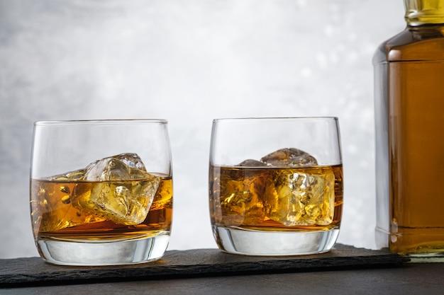 Крупный план виски с кубиками льда и бутылкой алкогольного напитка на сером фоне