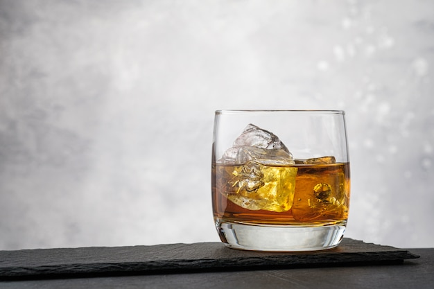Close-up whiskey with ice cubes on gray wall