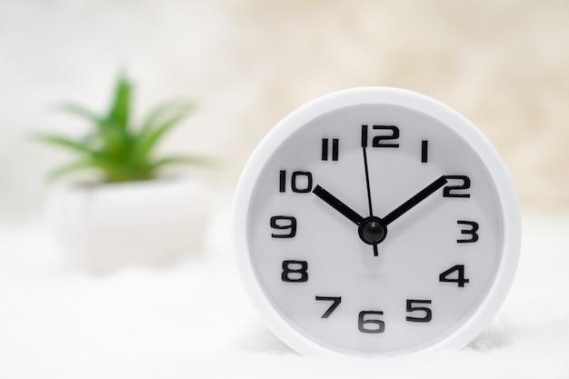 白い目覚まし時計とテーブルの上の小さな装飾的なtreein花瓶を閉じます