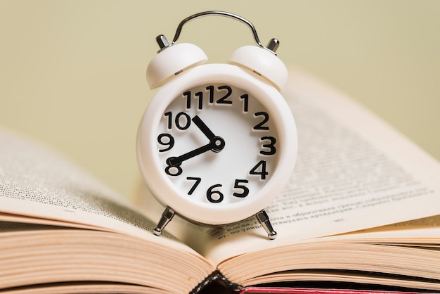Close-up of white alarm clock on an open book