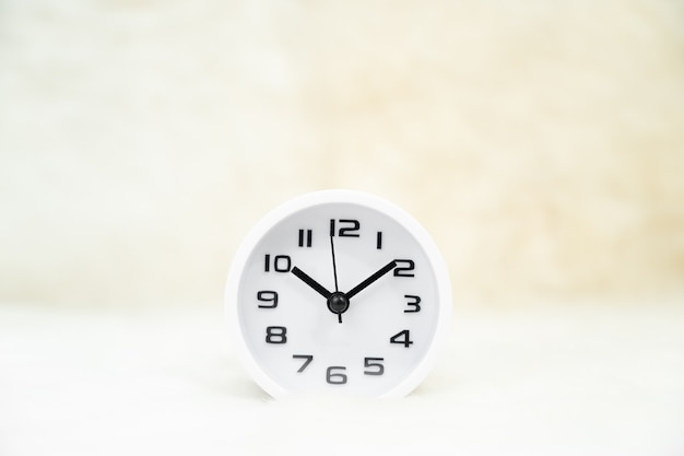 Close up white alarm clock on table,  minimalism concept