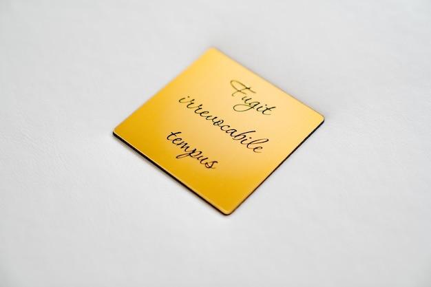 Закройте вверх. белая книга в кожаном переплете с золотой металлической вставкой с надписью на латыни - время невозвратное. полиграфическая продукция. фотоальбомы и альбомы. отдельные продукты.