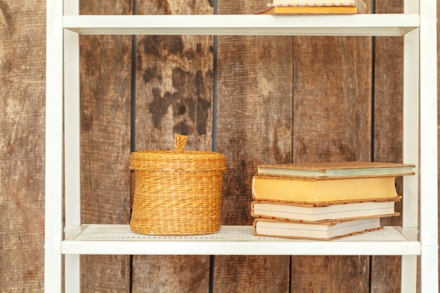 Close up of white bookshelf against grunge wooden wall