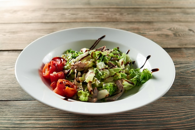 Close-up of a white bowl on the wooden table,served with light summer vegetable salad with chicken,paprika and lettuce leaves. looks delicious and tasty.