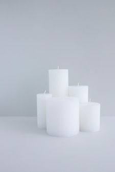 Close-up of white candles against grey background