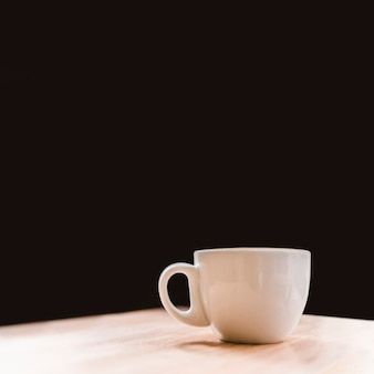 Close-up of white coffee cup on desk over black backdrop