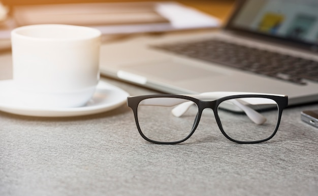 Close-up of white coffee cup and eyeglasses in front of laptop on gray background