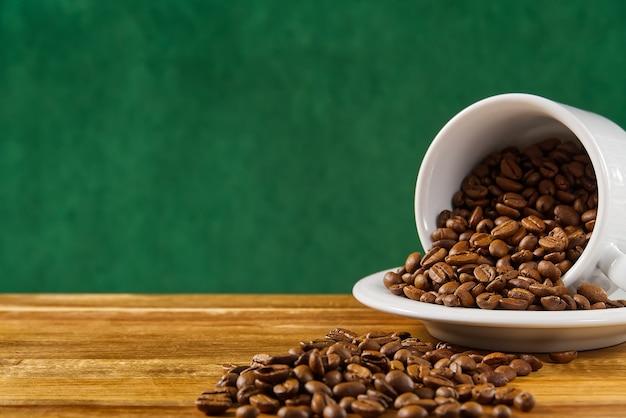 Крупным планом белая кофейная чашка, полная кофейных зерен на темно-зеленом фоне