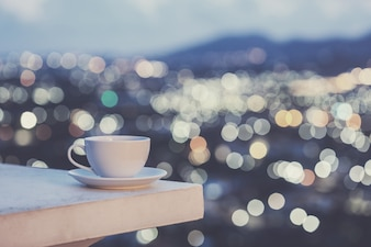 Close up white coffee cup on counter and colorful blur light bokeh of city background