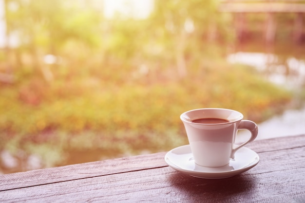 Close up white coffee cup on table in garden with blur light bokeh