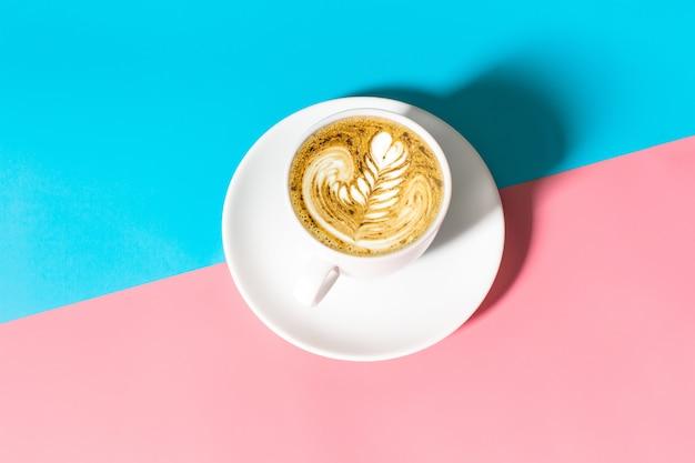 青とピンクのテーブルの上に白いコーヒーカップを閉じる、青とピンクのテーブルの上に分離されたブラックコーヒーの白いカップ