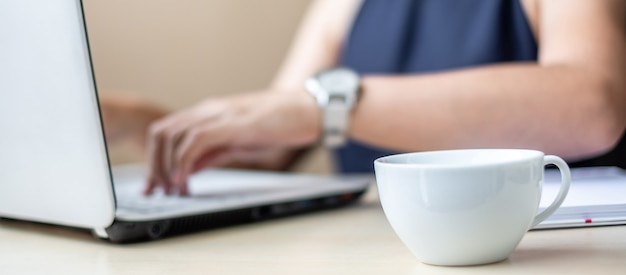 Close up white coffee cup with young businesswoman using laptop