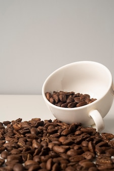 Close-up white cup filled with coffee beans