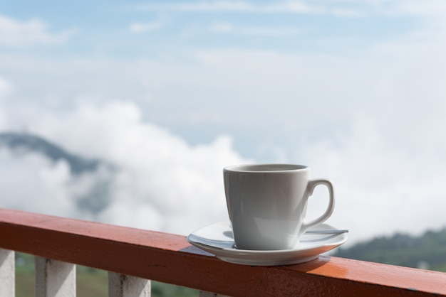 Close up white cup of hot coffee on balcony edge with outdoor natural green background