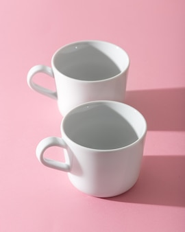 Close up of white cups on a pastel pink background