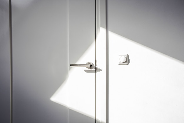 Close-up white door with sunlight. chrome door ,the light switch on the wall modern design empty and clean
