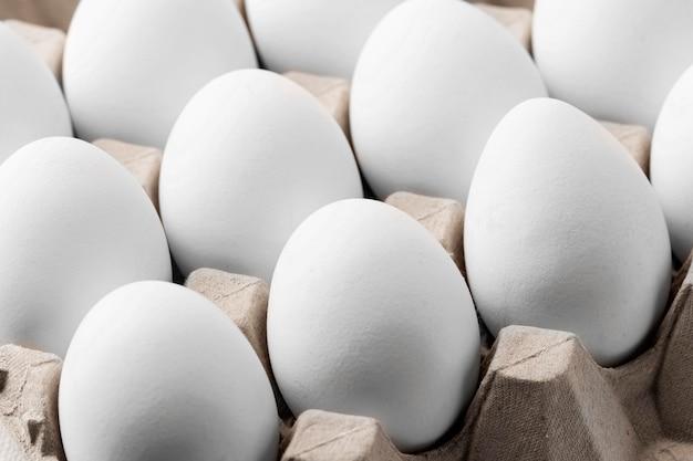 Крупный план белых яиц в коробке