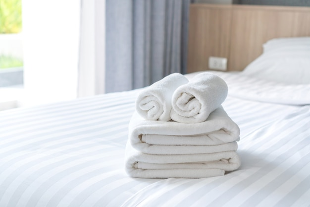 Close up of white fluffy, rolled towels on bed in hotel room for customer.