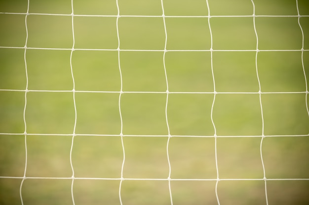 Close up of white football / soccer goal net with green grass as background using as sport wallpaper or background.