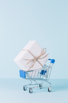 Close-up of white gift box in shopping cart on blue background