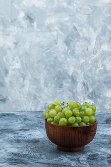 濃い水色の大理石の背景にボウルに白ブドウをクローズアップ。垂直