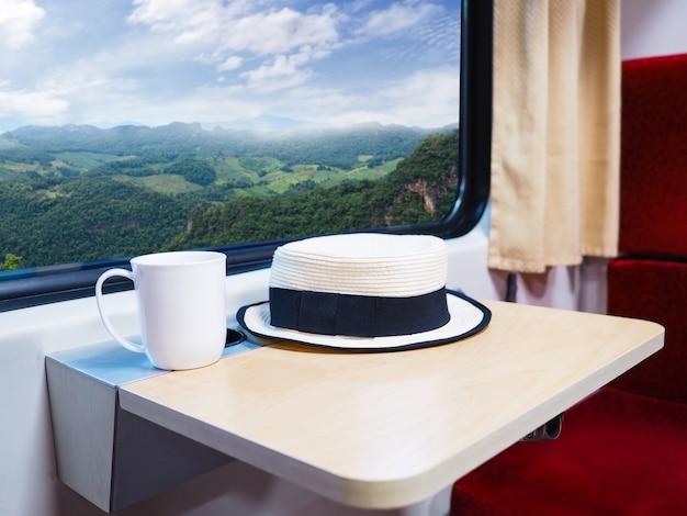 Закройте белую шляпу и чашку кофе на небольшом складном столике рядом со стеклянным окном в поезде с видом на горный пейзаж. с праздником отпуск концепции.