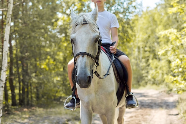 Close up of white horse running with teenage rider boy