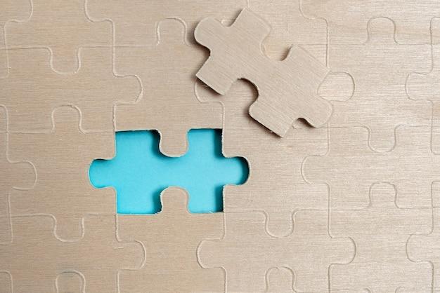 クローズアップの白いジグソーパターンのパズルのピースは、さまざまなテクスチャと紙の付属品を備えた平らな敷設の背景に配置された最後のピースが欠落していると接続されます