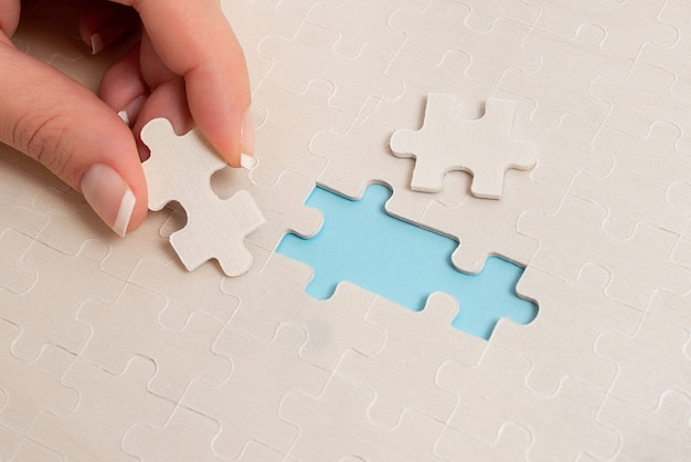 Белые кусочки пазла крупным планом, которые нужно соединить с отсутствующим последним элементом, расположенным на плоском фоне с разной текстурой и принадлежностями для бумаги Premium Фотографии